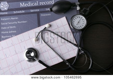 Blood pressure meter and stethoscope, on dark wooden background