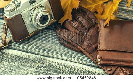 Leather Wallet And Gloves With Vintage Camera Over Wooden Background