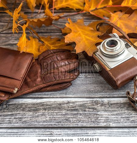 Leather Wallet With Gloves And Camera On Wooden Background