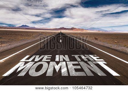 Live in the Moment written on desert road