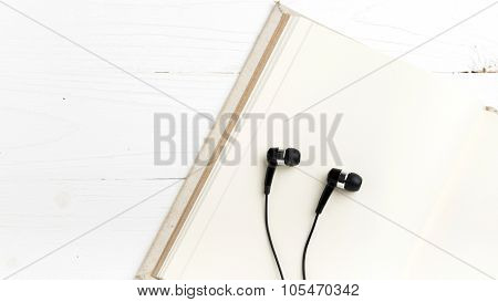 notebook and ear phone over white table
