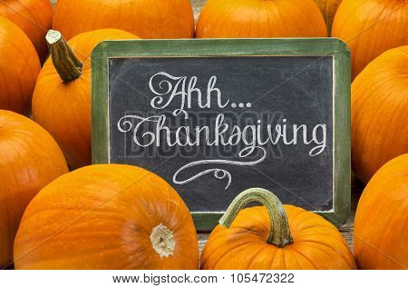 Ahh ... Thanksgiving - white chalk handwriting on a vintage slate blackboard surrounded by pumpkins, Thanksgiving concept