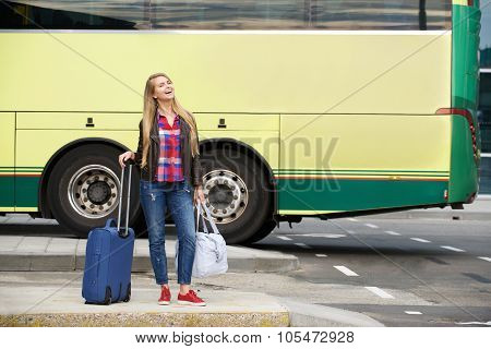 Smiling Travel Woman Standing At Bus Terminal With Bags