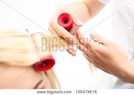 The woman at the hairdresser, twirling hair curlers