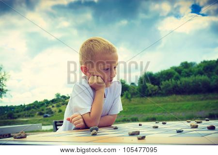 Little Boy Clever Child Playing Checkers In Park