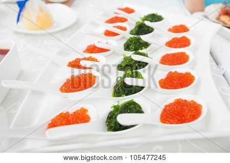 Red Caviar Close-up In White Spoons On Banquet