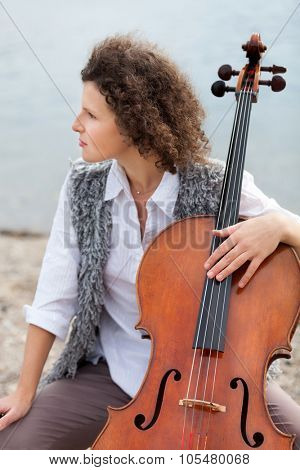 closeup of a young woman with her cello, outdoor