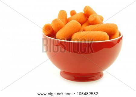 prepared carrots in a red ceramic bowl on a white background