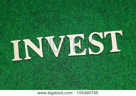 The Invest word on rusty green background. Business concept