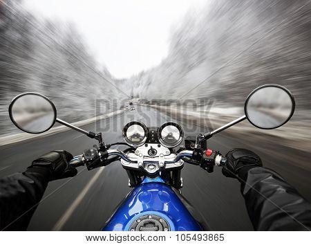 Man driving on moto on big speed on asphalt road at winter