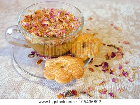 Gentle composition of the drink of tea rose petals, transparent cup and saucer and cookies