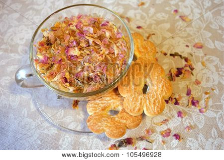 drink of tea rose petals, transparent cup and saucer, cookies in the shape of flowers