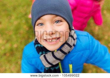 childhood, leisure, autumn and people concept - happy little boy face outdoors
