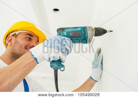 building, working equipment and people concept - close up of happy builder in hardhat perforating wall with drill indoors