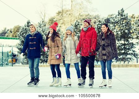 people, winter, friendship, sport and leisure concept - happy friends ice skating and holding hands on rink outdoors