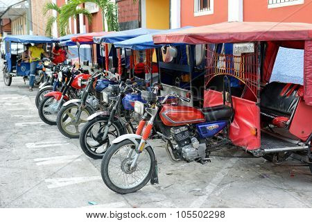 IQUITOS, PERU - OCTOBER 17, 2015: MotoKars parked in a line. The motorcycle with passenger cab attached is a common form of transportation in the remote Amazon city.