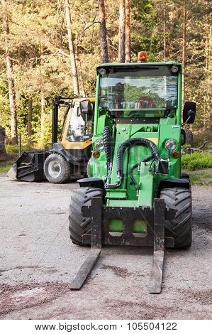 Green Small Forklift Stands On A Logging Area