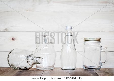 Assorted Glass Bottles On A White Washed Wooden Table. Clear Glass Bottles And Containers Of Various