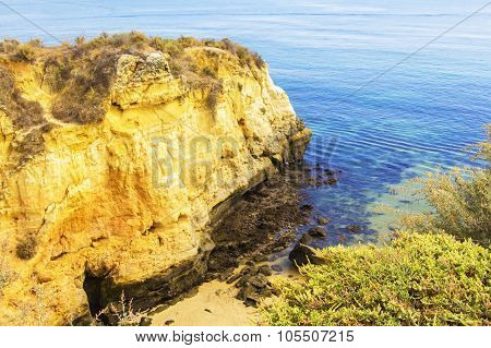 background landscape rocks and caves on the golden beach Praia do Pinhão in Lagos