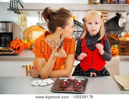 Girl In Bat Costume With Smiling Mother Eating Halloween Cookies