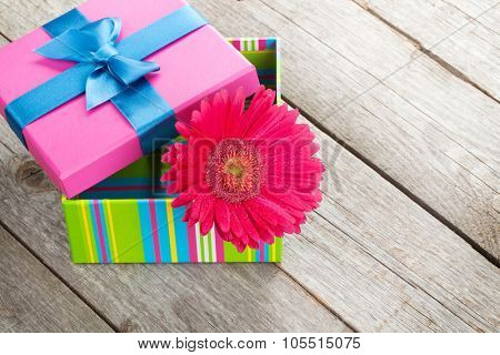 Purple gerbera flower in gift box on wooden table with copy space
