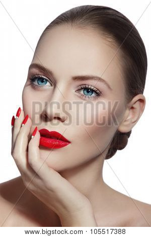 Close-up portrait of young beautiful woman with red lips and fancy manicure over white background