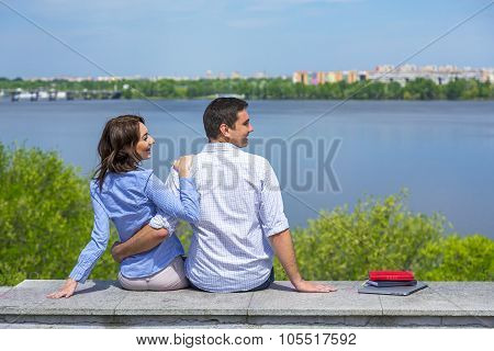 Young couple on parapet looking sideward