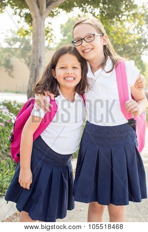 Two little girls with backpacks on their way to school