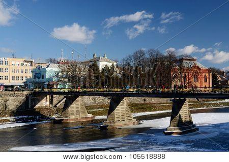 People crossing old pedestrian bridge over Uzh river in UzhhorodWestern Ukraine.City located at bord