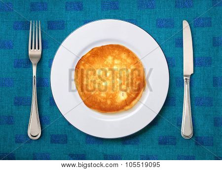 round white plate with cake, knife and fork on table