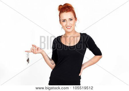 Young beautiful, red-haired woman, girl holding in his hands the keys of the house.He bought a house