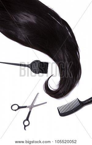 Black silky hair, hair dye brush, scissors, and hairbrush, isolated on white background