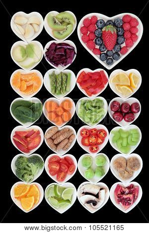 Healthy superfood vegetable and fruit selection in heart shaped porcelain dishes over black background, high in vitamins and antioxidants.