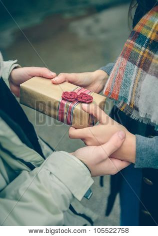 Man hands giving gift box to woman with scarf
