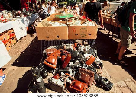 Many old photo cameras on the layout of a vendor on flea market