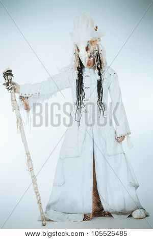 Artistic handsome man in a scenic suit of white raven. Ethnic costume. Isolated over white. Full length portrait.