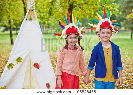 Adolescent friends in Indian headdresses looking at camera outdoors