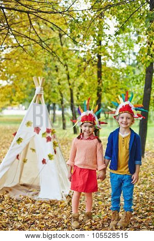 Happy girl and boy in Indian headdresses playing in autumn park