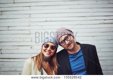 Happy young couple in casualwear looking at camera