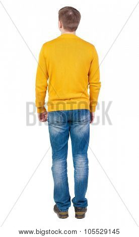 Back view of man in jeans. Standing young guy. Rear view people collection.  backside view of person.  Isolated over white background. The guy in the yellow jacket is hands down along the body.