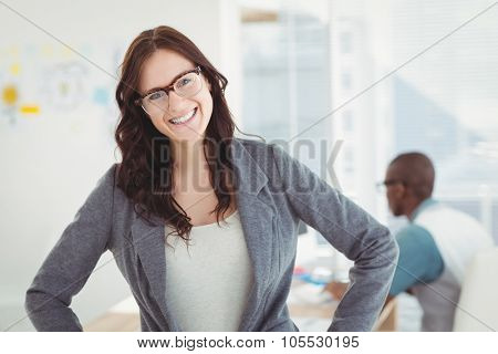 Portrait of smiling businesswoman wearing eyeglasses with hand on hip while standing in office