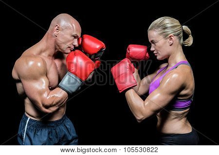 Side view of boxers with fighting stance against black background