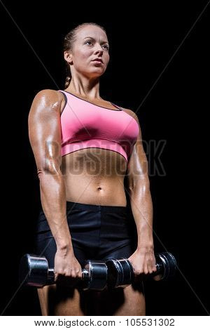 Low angle view of woman exercising with dumbbells against black background