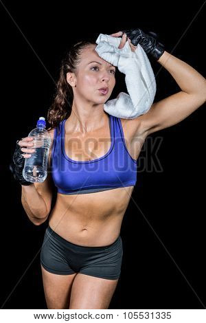 Exhausted woman wiping sweat while holding water bottle against black background