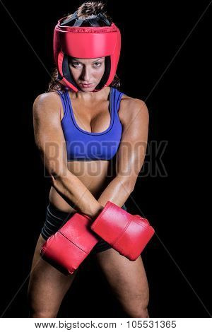 Portrait of fit female boxer standing against black background