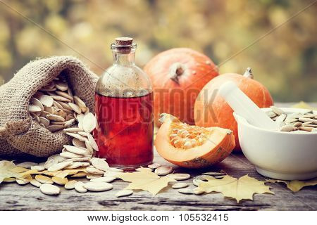 Pumpkin Seeds Oil Bottle, Pumpkins, Canvas Bag With Seeds And Mortar On Wooden Table.