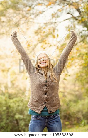 Smiling pretty woman with arms raised on an autumns day