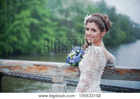 Portrait of a beautiful bride in white wedding dress smiling under rain