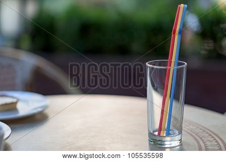 Empty glass with colored drinking straws