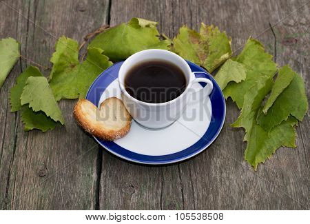 Cup Of Coffee On A Saucer, One Cookies, It Is Decorated With Grape Leaves, A Still Life